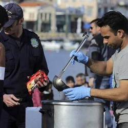 Lesvos island, volunteers on the port, offering meals to migrant newcomers by the aid of the Greek Coastguard